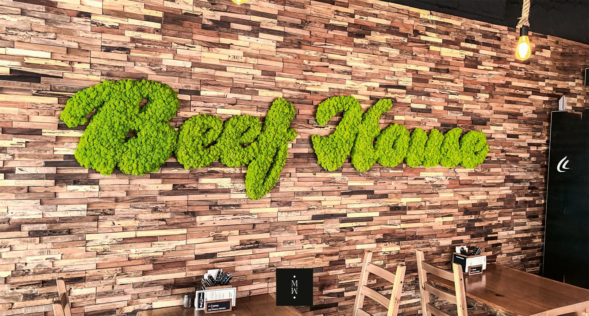 Logo des Restaurants Beef House aus apfelgrünem Isalndmoos an eienr Ziegelwand