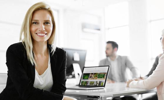 MoosMoos Verkäuferin sitzt am Koferenztisch mit aufgeklapptem Laptop und lächelt